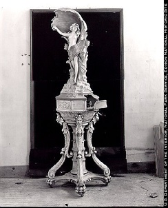 Phonograph cabinet built with Edison cement, 1912. The clockwork portion of the phonograph is concealed in the base beneath the statue; the amplifying horn is the shell behind the human figure.