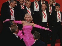 Monroe in Gentlemen Prefer Blondes. She is wearing a shocking pink dress with matching gloves and diamond jewellery, and is surrounded by men in tuxedos