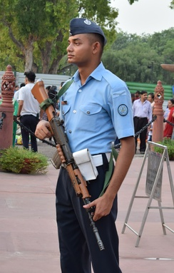 An Aircraftsman of the Indian Air Force with his uniform, Shoulder Rank Patch and INSAS rifle standing guard at the India Gate memorial at New Delhi.
