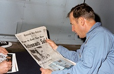 Lovell reads a newspaper account of Apollo 13's safe return aboard recovery vessel USS Iwo Jima.