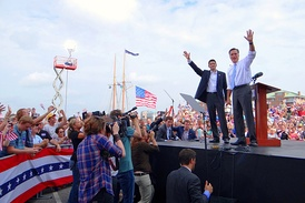 Mitt Romney and Paul Ryan seen in medium distance on an outdoor stage, with large crowd around them