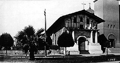 Mission San Francisco de Asís around 1910. The wooden addition has been removed and a portion of the brick Gothic Revival church is visible at right. The large stone church was severely damaged in the 1906 earthquake.[1]
