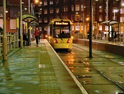 Metrolink operating at night (left) and in December snow (right), at Shudehill Interchange and Radcliffe tram stop respectively.