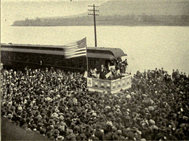 A dramatic political scene. Beside a river stands a podium, on which a flagpole flies a huge American flag. Beneath the flag stands a candidate in a dark suit addressing an impressive crowd which takes up most of the photograph. Not only the quayside but a ferry beside it on the water are packed full of people listening intently.
