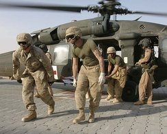 Marines unload a wounded comrade from an Army UH-60 Blackhawk helicopter for medical treatment at Al Qaim.