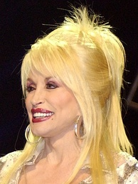 A woman with blond hair wearing large hoop earrings and red lipstick.