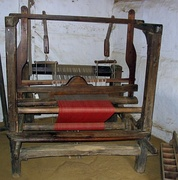 Hand loom at Hjerl Hede, Denmark, showing grayish warp threads (back) and cloth woven with red filling yarn (front)