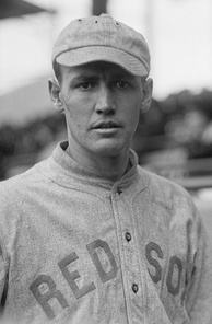 "A man in a gray baseball uniform looks into the camera; he is wearing a gray baseball cap on his head and his jersey reads ""Red Sox"" in block type across the chest."