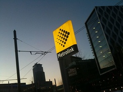 Metrolink stops are marked with yellow totems, such as this one at MediaCityUK