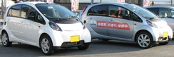 Two Mitsubishi i kei cars photographed together in Japan. The silver i is a dealer model for customers to test drive.