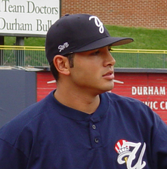 A man in a blue shirt and navy blue hat looks off to the side.