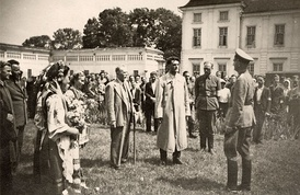 People, some of them in Ukrainian national dress, greeting Nazi Soldiers in 1941
