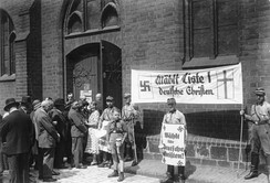 Stormtroopers holding German Christian propaganda during the church council elections on 23 July, 1933 at St. Mary's Church, Berlin. After that internal struggles, controversies, reorganization and splits struck the German Evangelical Church