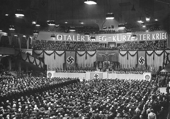 "Sportpalast speech, 18 February 1943. The banner says ""TOTALER KRIEG – KÜRZESTER KRIEG"" (""Total War – Shortest War"")"