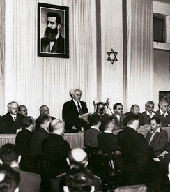David Ben-Gurion proclaiming independence beneath a large portrait of Theodor Herzl, founder of modern Zionism
