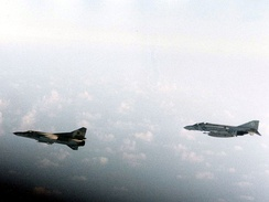 "A U.S. Navy McDonnell F-4J Phantom II of Fighter Squadron VF-74 ""Be-Devilers"" escorting a Libyan Mikoyan-Gurevich MiG-23 over Gulf of Sidra in August 1981."