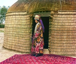 Full-length profile portrait of Turkman woman, standing on a carpet at the entrance to a yurt, dressed in traditional clothing and jewelry