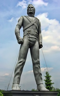 Silver-colored statue of Jackson standing up with his arms bent inward and both legs spaced apart.