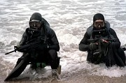 Two SEALs in diving gear scout a beach during an exercise.