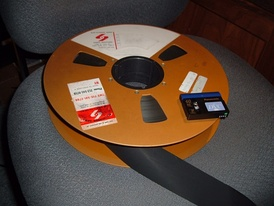 A fourteen-inch reel of 2-inch quad videotape compared with a modern-day MiniDV videocassette. Both media store one hour of color video.