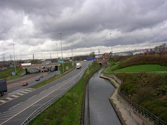 View from a bridge over a canal, with a motorway running to the left. The sky is dark and overcast.