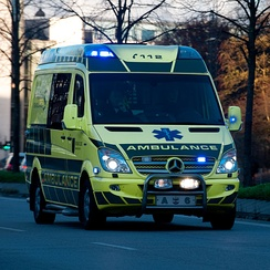 An ambulance in Denmark with roof-integrated LED lights, plus side-view mirror, grill and front fend-off lights, and fog lamps wig-wags