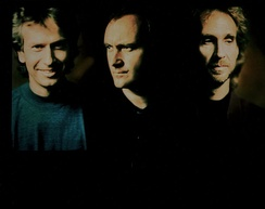 Collins (middle) with his two Genesis bandmates, Tony Banks (left) and Mike Rutherford (right) in 1991. Collins toured with Genesis the following year, his last with the band until 2007