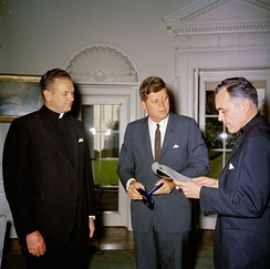 Rev. Theodore Hesburgh presents the 1961 Laetare Medal to President John F. Kennedy. Fr Edmund P. Joyce to the side.