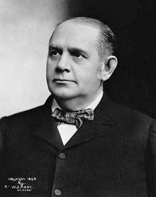 A black-and-white head-and-shoulders photograph of a respectfully turned-out middle-aged gentleman in a tartan-pattern bow-tie, white shirt and dark jacket