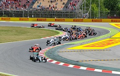 A picture of the 2015 field of formula one cars negotiating the first turns during the 2015 Spanish Grand Prix.
