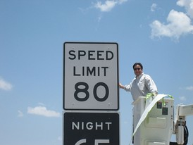 Texas Legislator Pete Gallego unveiling a new 80 mph speed limit sign on Interstate 10 near Fort Stockton, Texas. Note that night speed limits have been abolished since this photo was taken.