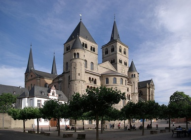 A huge cathedral with numerous towers, both square and round, rises above a town square where people are sitting in the shade of clipped trees.