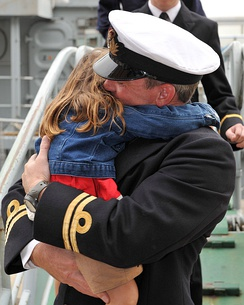 A Royal Navy Officer hugs his daughter after returning from a long deployment on HMS Chiddingfold