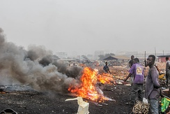 A metal scrap worker is pictured burning insulated copper wires for copper recovery at Agbogbloshie, Ghana.