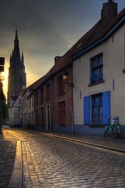 An old street in Bruges, with the Church of Our Lady tower in the background
