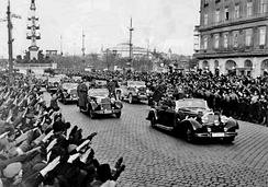 Crowds greet Adolf Hitler as he rides in an open car through Vienna in March 1938