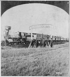 Directors of the Union Pacific Railroad gather on the 100th meridian, which later became Cozad, Nebraska, about 250 miles (400 km) west of Omaha in the Nebraska Territory, in October 1866. The train in the background awaits the party of Eastern capitalists, newspapermen, and other prominent figures invited by the railroad executives.