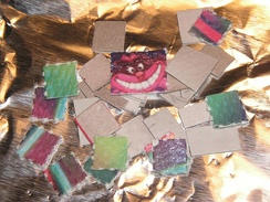 Several LSD blotters, one of which features the Cheshire Cat's face as depicted in the 1951 film