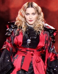 A blonde woman wearing a black dress with a red armor-like jacket and a microphone on her bosom.