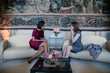 Michelle Obama and Carla Bruni share a laugh while seated on adjacent couches.