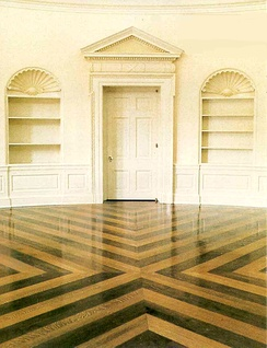 Oval Office floor, replaced during the administration of Ronald Reagan. Designed by Nancy Reagan, the installation is arranged in a contrasting cross pattern of quarter sawn oak and walnut.