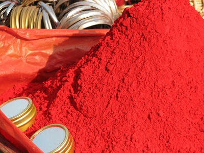 Vermilion is similar to scarlet, but slightly more orange. This is sindoor, a red cosmetic powder used in India; Some Hindu women put a stripe of sindoor in their hair to show they are married.