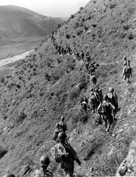 U.S. Marines move out over rugged mountain terrain while closing with North Korean forces.