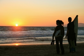 A young couple watching the sunset on a Los Angeles beach with surfboard in hand