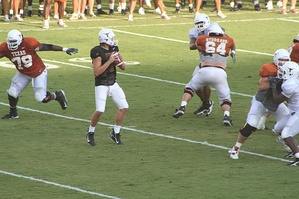 A quarterback at practice, dropping back to pass.