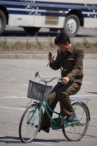 North Korean man riding a bike in Hamhung while using a cellphone.