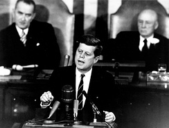 President John F. Kennedy addresses a joint session of Congress, with Vice President Lyndon B. Johnson and House Speaker Sam Rayburn seated behind him