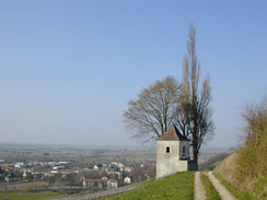 An old stone watch tower stands at a mountain top road; past the road, layers of rounded hilltops illustrate the kind of terrain the combatants faced. In the distance a silvery shimmer on the horizon marks the location of the Rhine river.