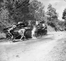Men of the 2/6th Battalion, Queen's Royal Regiment (West Surrey) advance past a pair of burning German PzKpfw IV tanks in the Salerno area, 22 September 1943.