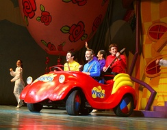 The Wiggles' lineup in 2007, riding in the Big Red Car during a concert